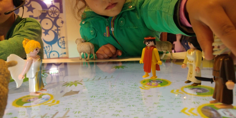 Close-up image of a horizontal screen. On top of the screen, which functions as a table, are human figurines. A child reaches her arm across the table to reposition one of the figurines.