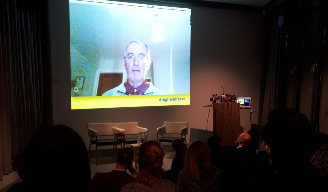 Graham Black is seen on a screen, addressing the crowd attending Night Shift