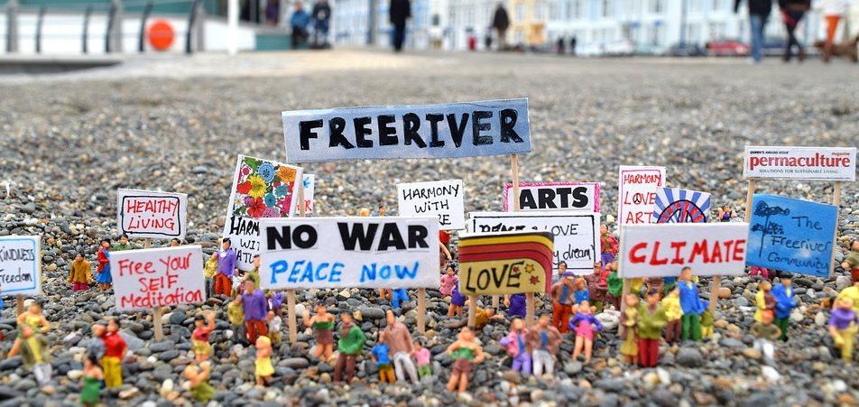 Een close-up foto van een mini-protest. Kleine poppetjes houden allerhande protestborden omhoog.
