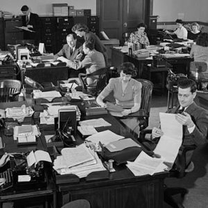 a picture of people doing important things in an office setting ca. 1943.
